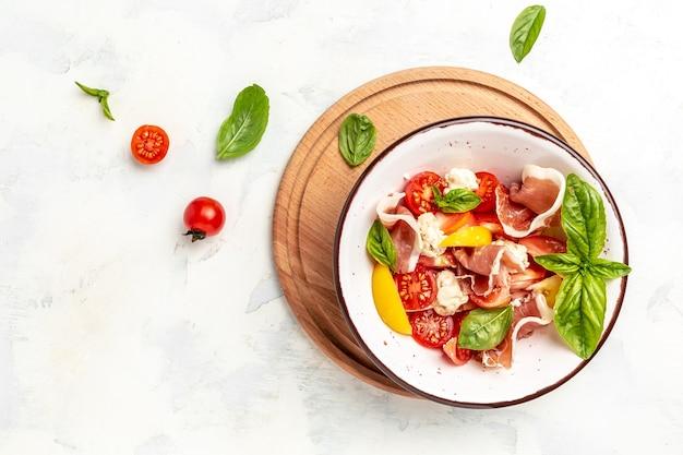 Салат с помидорами, шариками из сливочного сыра, ветчиной ветчины и листьями базилика на светлом фоне. детокс и концепция чаши здоровых суперпродуктов. вид сверху