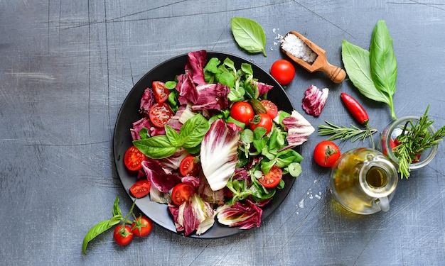 Salad with tomatoes and radicchio leaves, basil  with olive oil and rosemary.