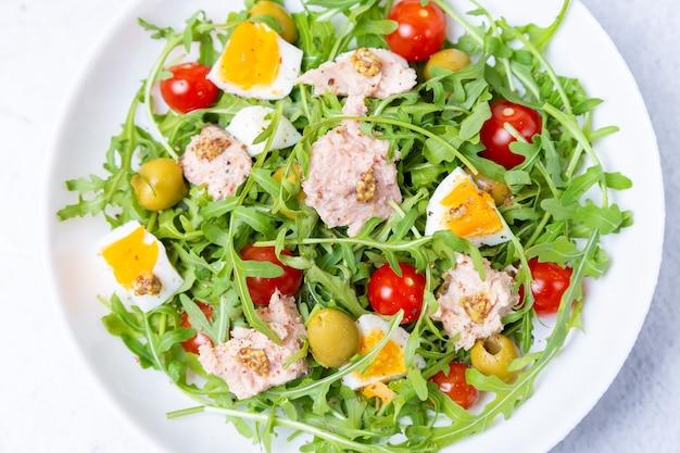マグロ、ルッコラ、トマト、オリーブ、卵の白いプレートのサラダ。伝統的な料理。閉じる。