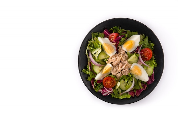 Salad with tuna, egg and vegetables on white