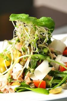 Салат с тунцом на тарелке над деревянным столом
