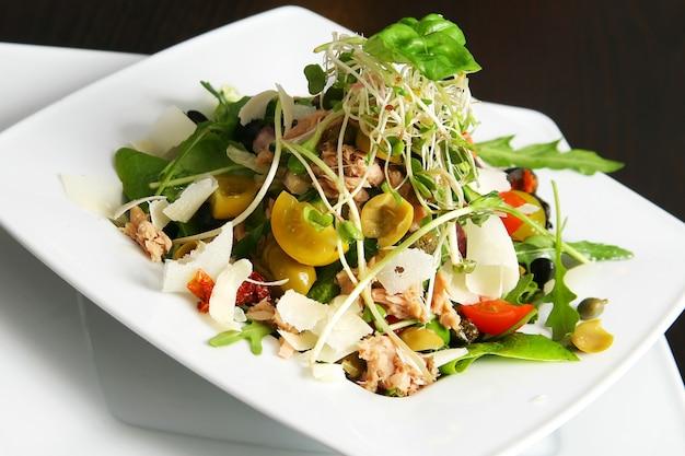 Салат с тунцом на тарелке над столом