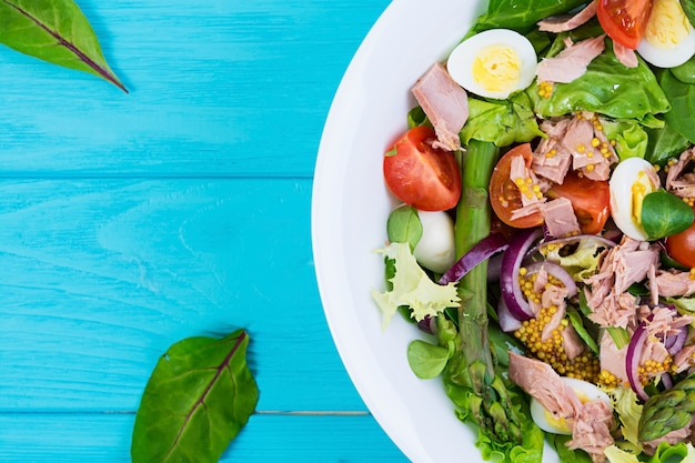 Salad with tuna, tomatoes, quail eggs, asparagus and onions on wooden