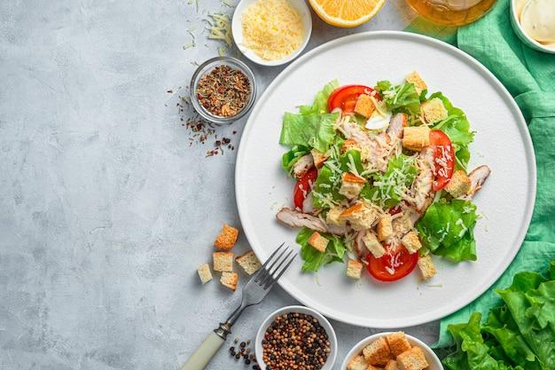 회색 배경에 야채와 닭 가슴살 샐러드. 전통적인 시저 샐러드. 건강한 영양의 개념.
