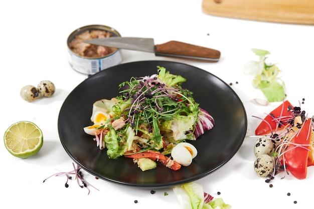 Салат с овощами и рыбой в красивой тарелке