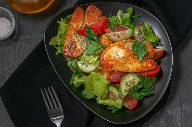 Салат с овощами и жареным сыром халуми со специями. на черной тарелке. рядом с тарелкой вилка и баночки со специями с маслом. вид сверху. темный фон.