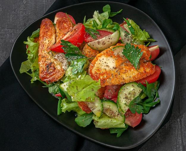 Салат с овощами и жареным сыром халуми со специями. на черной тарелке. вид сверху. темный фон.