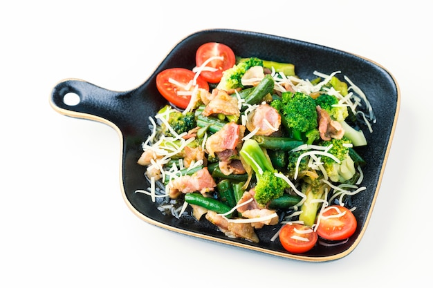 Salad with vegetables and bacon in bowl on white background.