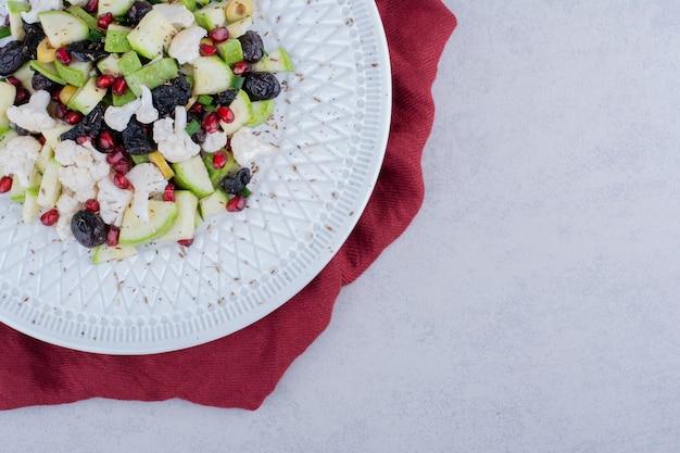 Insalata con verdure, olive nere e chicchi di melograno