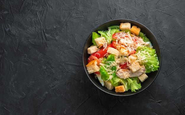 Salad with vegetables, chicken breast and crackers on a black background. culinary background with space to copy. healthy food.