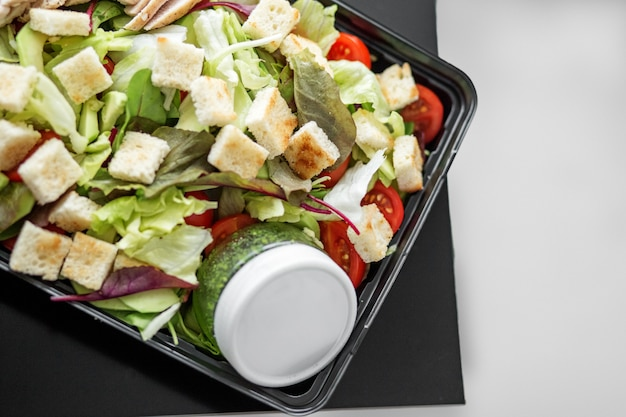 Salad with vegetables and chicken and pesto sauce in lunch box.