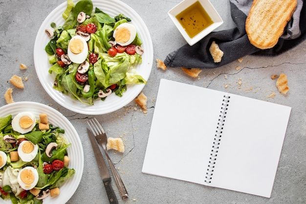 Salad with vegetables and eggs beside notebook