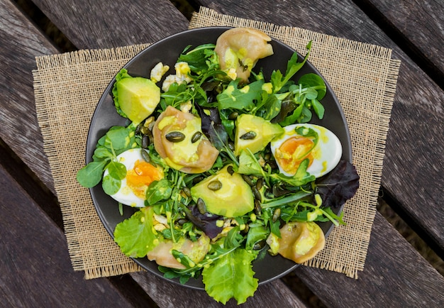 Salad with vegetables, eggs and greens on wooden table