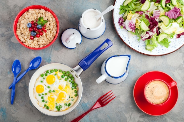 Salad with vegetables, eggs, oatmeal porridge, croissants and coffee