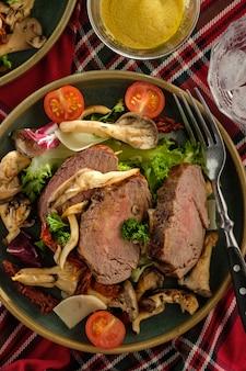 Салат из теплой говядины с вешенками, помидорами и зеленью. вид сверху