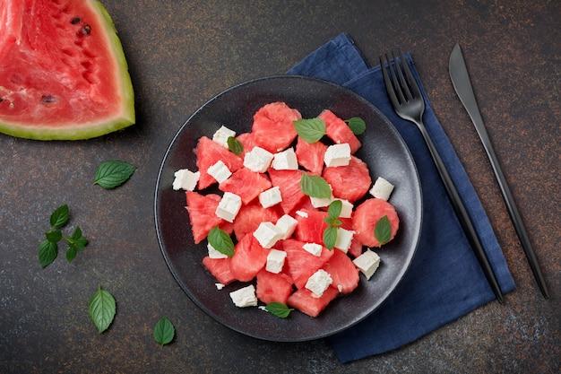 Салат с арбузом и сыром фета на черной тарелке