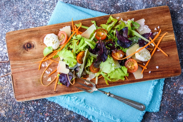Salad on a wooden board with a napkin.