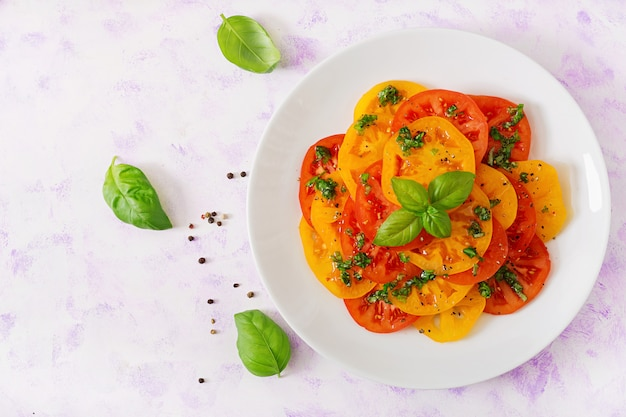 Salad of yellow and red tomato with basil pesto on a light table. flat lay. top view