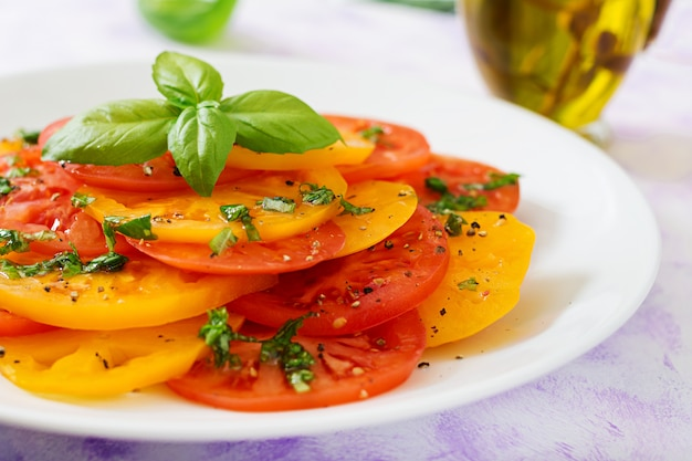 Salad of yellow and red tomato with basil pesto on a light table.