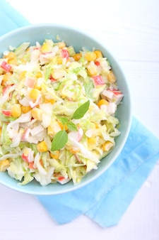 Salad of young cabbage with corn and crab sticks in blue bowl