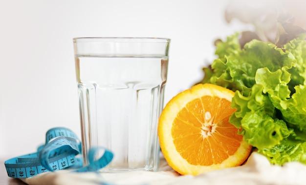 サラダの葉。オレンジ、一杯の水と白い背景の上の青いテープの測定、健康的なライフスタイルと飲料水の概念