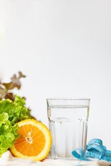サラダの葉。オレンジ、一杯の水、テキスト、健康的なライフスタイル、飲料水の概念のためのコピースペースと白い背景の上の青いテープを測定