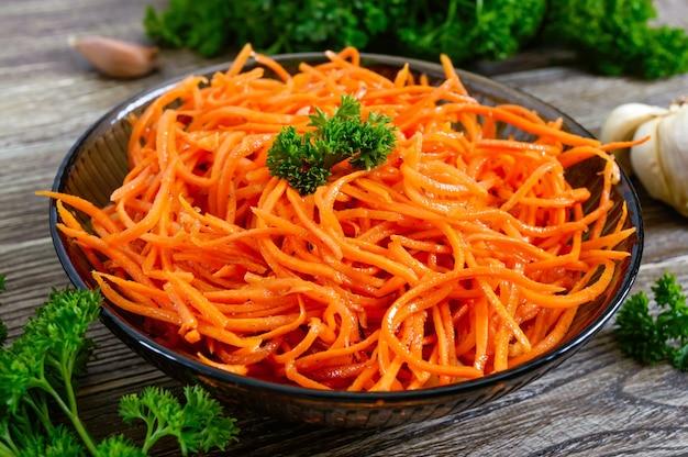 Салаты из свежей моркови. корейский пряный салат из овощей в миске на деревянном столе. витаминное меню. веганская кухня.