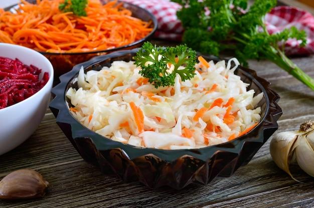 Салаты из свежих овощей: капуста, морковь, свекла. корейские острые салаты в мисках на деревянном столе. витаминное меню. веганская кухня.