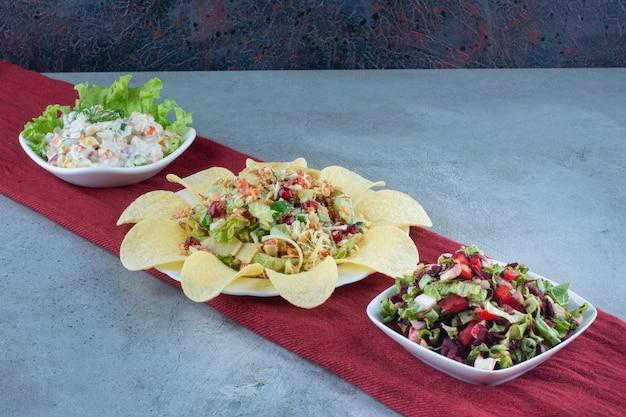 Салаты, украшенные листьями салата и картофельными чипсами на мраморном столе.