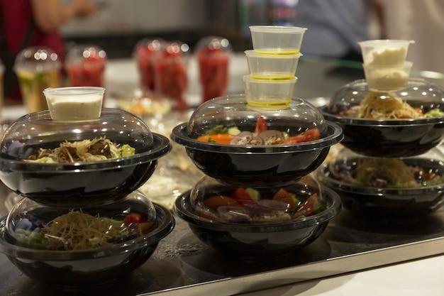 Салаты в одноразовой пластиковой посуде с соусами в магазине. доставка онлайн. крупный план.