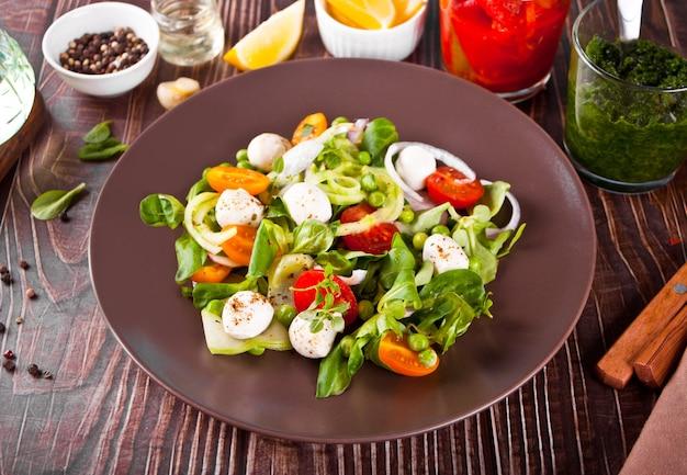 新鮮なチェリー トマト、モッツァレラ、バジル、大根、その他の野菜のサラダ ディナー テーブル