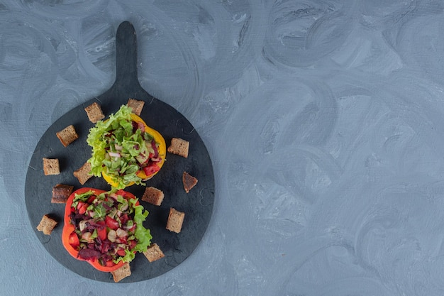 Insalate porzionate in fette di peperone su un vassoio da portata su sfondo di marmo.