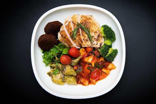 Salads and various vegetables are on the white plate the background is black