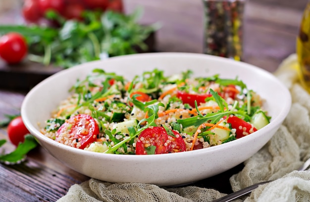 Salads with quinoa,  arugula, radish, tomatoes and cucumber in bowl on  wooden table.  healthy food, diet, detox and vegetarian concept.