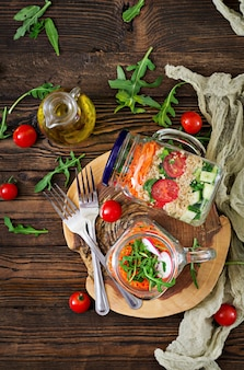 Salads with quinoa,  arugula, radish, tomatoes and cucumber in glass  jars on  wooden table.  healthy food, diet, detox and vegetarian concept. top view. flat lay