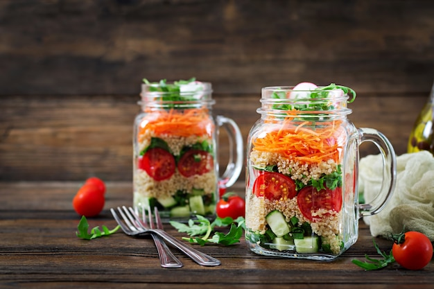Salads with quinoa,  arugula, radish, tomatoes and cucumber in glass  jars on  wooden table.  healthy food, diet, detox and vegetarian concept