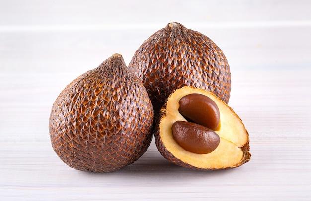 Salak (salacca zalacca) 또는 나무 배경에 고립 된 뱀 과일