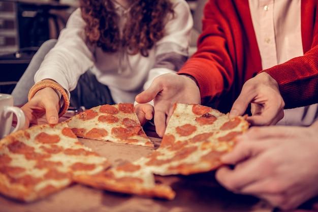 サラミとチーズ。サラミとチーズと一緒においしいピザを食べる3人の空腹のアクティブな音楽の学生