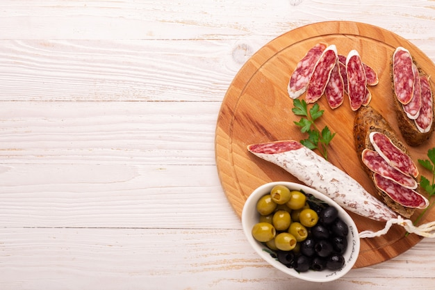 Salami and bread on white wooden background. top view.