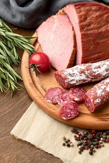 Salami and fillet meat on wooden board close-up