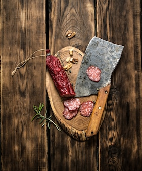 Salami and an old hatchet with rosemary. on wooden background.