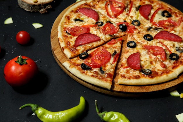 Salami pizza topped with fresh tomato and olive slices close-up view