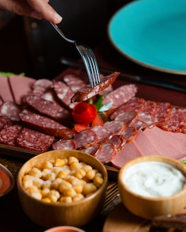Salami plate with sausage slices derved with saltypeas, sauce on wooden board