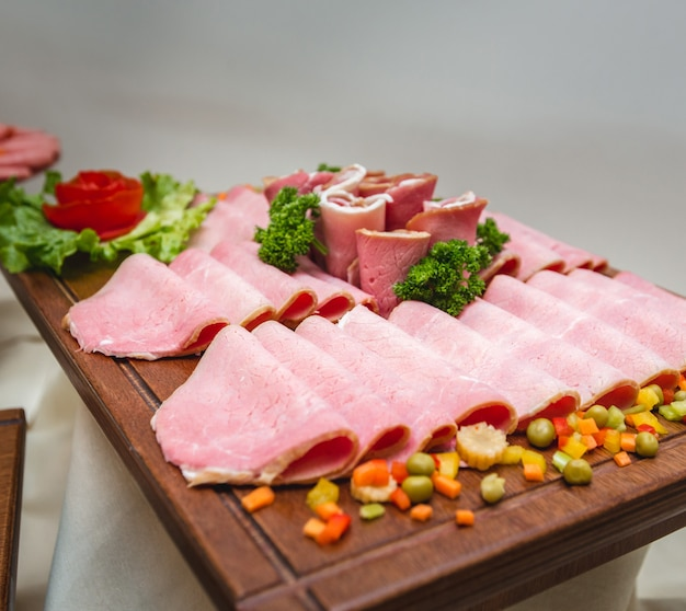Salami sausage platter with wide selection of charcuterie foods and vegetables.