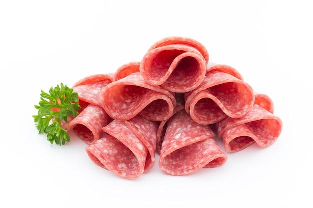 Ломтики колбасы салями, изолированные на белом фоне.