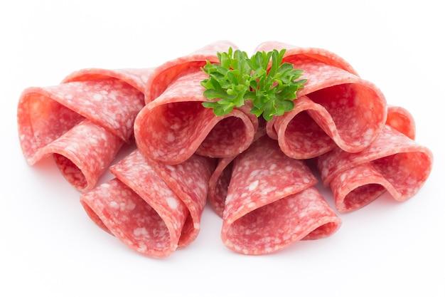 Ломтики колбасы салями, изолированные на белом фоне. Premium Фотографии