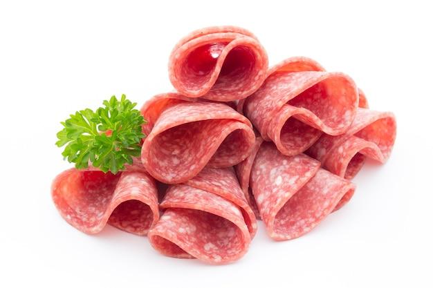 Ломтики колбасы салями, изолированные на белом.