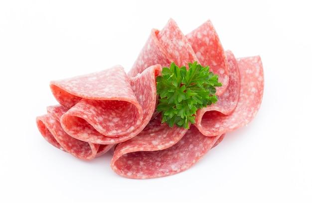 Изолированные куски колбасы салями. Premium Фотографии
