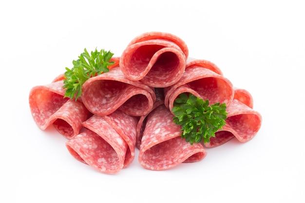 Изолированные куски колбасы салями.