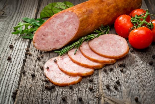 Колбаски салями нарезанные с перцем, чесноком и розмарином на разделочную доску на деревянный стол